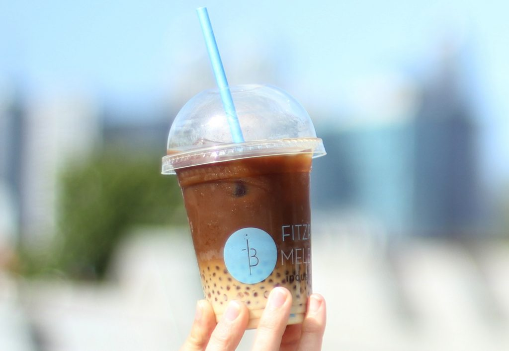 An iced coffee cup with a layered drink inside - light coffee milk on the bottom and dark coffee on top.