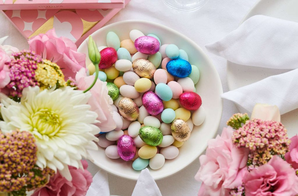A table set with a white plate filled with colourful Easter eggs, surrounded by flowers and a white table cloth