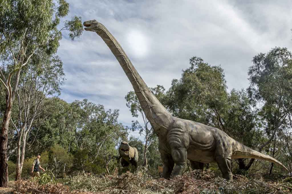 A dinosaur like creature standing in a park