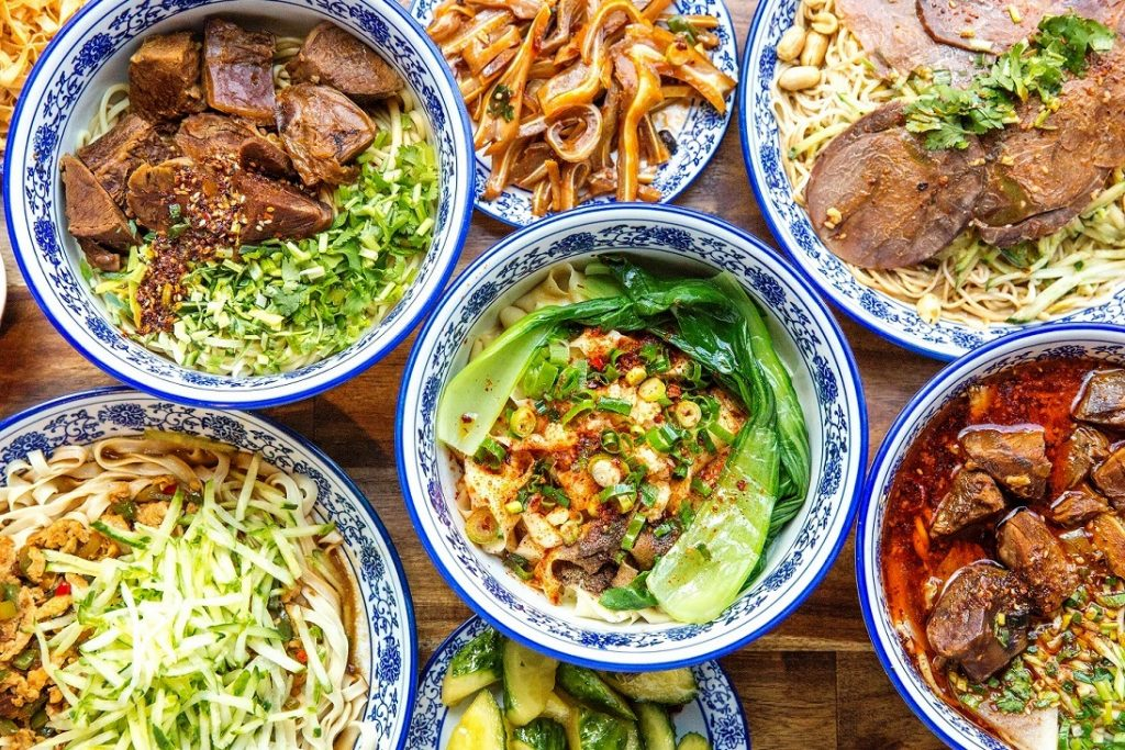 Dining table showing six different plates of noodle dishes and sides at Lanzhou beef noodle