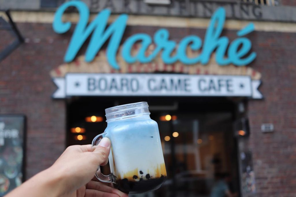 Someone holding a glass mason jar filled with bubble tea in front of a large brick building