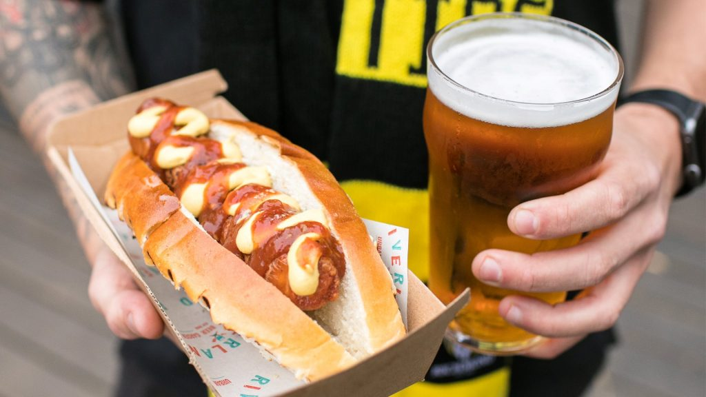 A man's hands holding a sausage in a bread roll and a large glass of beer