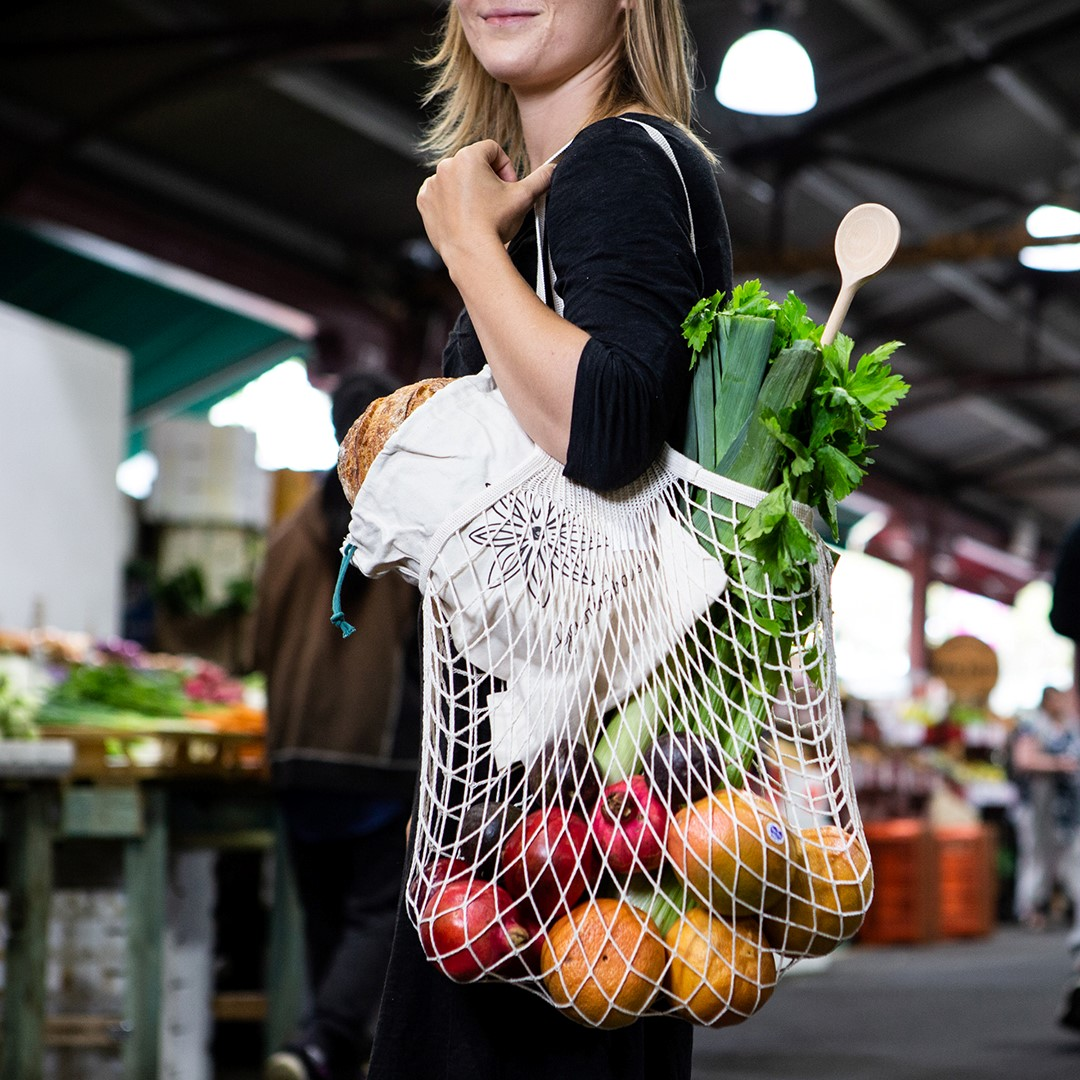 A woman holding a bag with fruit and vegetables in in it at a market