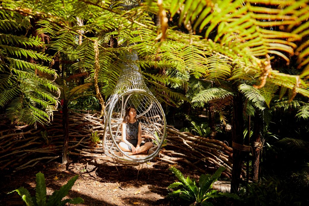 A human sized metal bird's nest seat with a person sitting in it, set amongst a leafy green garden