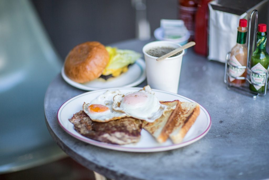 A plate of food featuring fried eggs on toast, a coffee and a burger in the background
