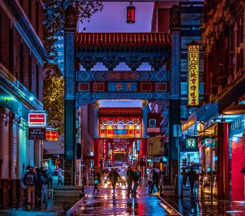 Chinatown street at night with neon signs, a hanging lantern and people walking