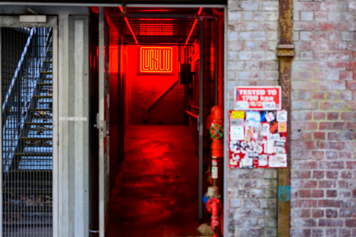 A red neon sign at the end of a corridor