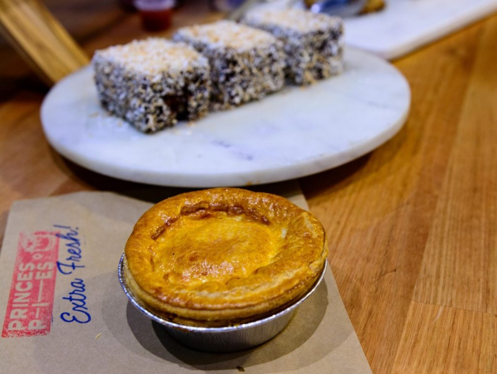 A pie on a brown paper bag with a plate of lamingtons behind it