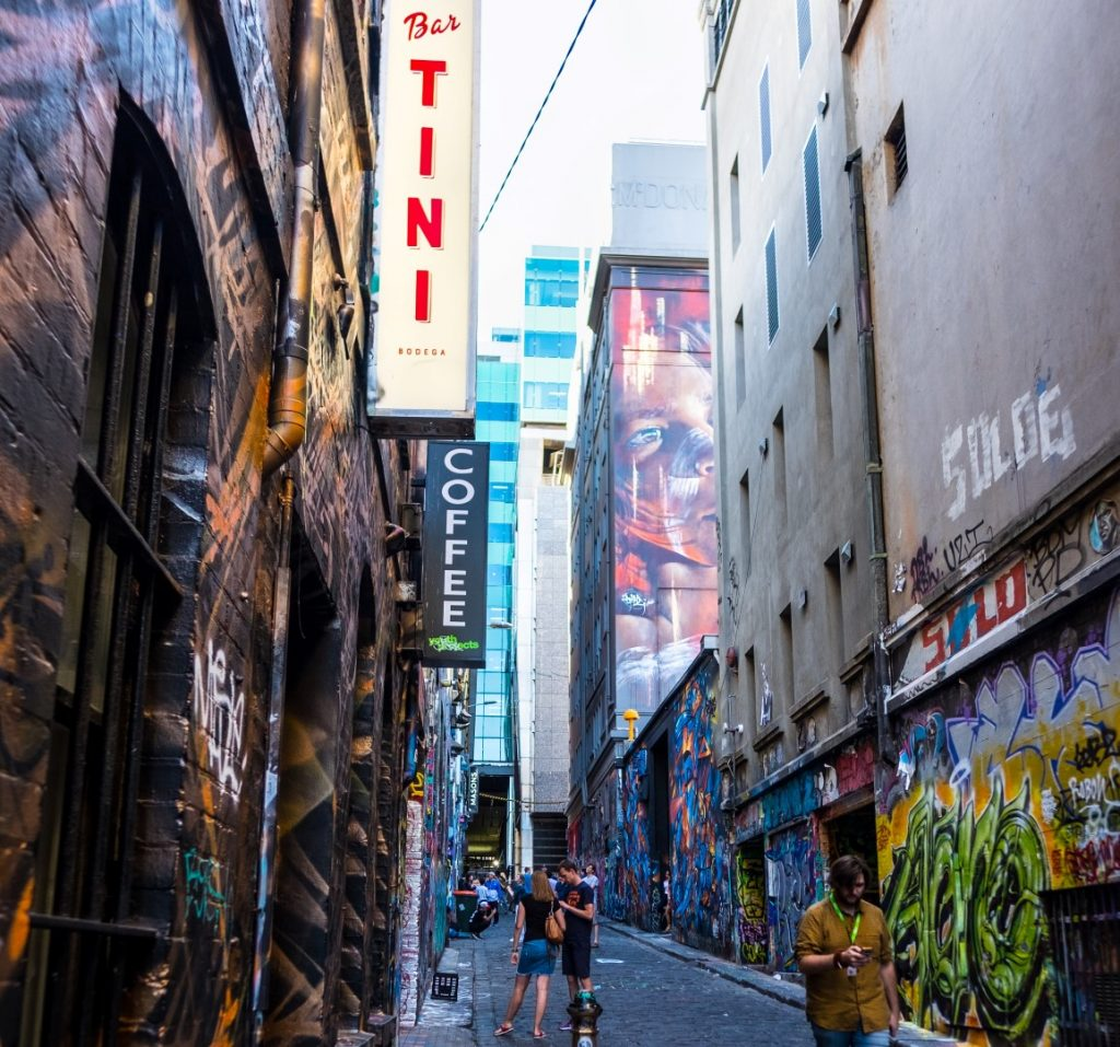 People taking photos in a street art covered laneway