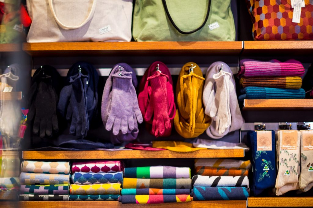 Brightly coloured scarves and gloves on display in a shop
