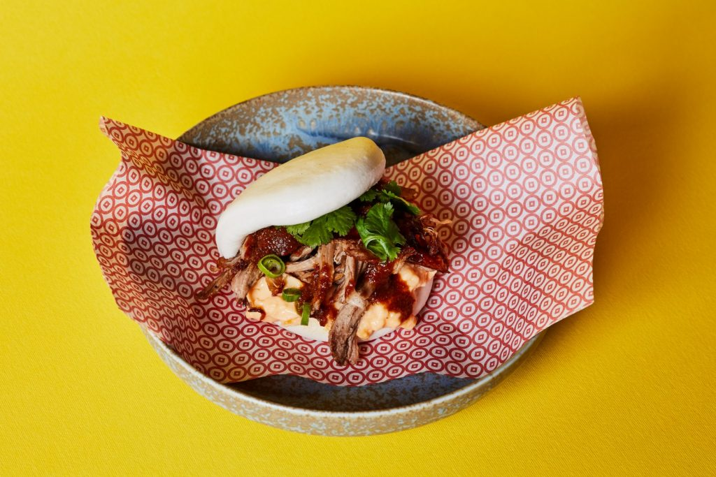 An asian bao with peking duk and scrambled eggs on a pink napkin