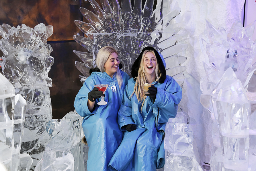 Two women sitting on a large ice sculpture in the shape of a throne, both wearing blue jackets and sipping cocktails