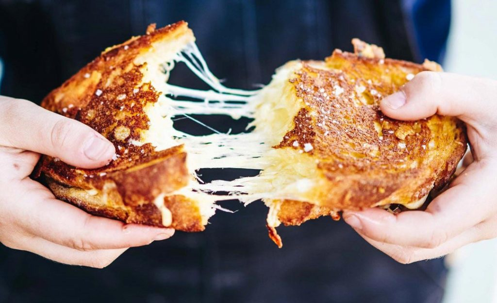 A melted cheese toasted sandwich being pulled apart