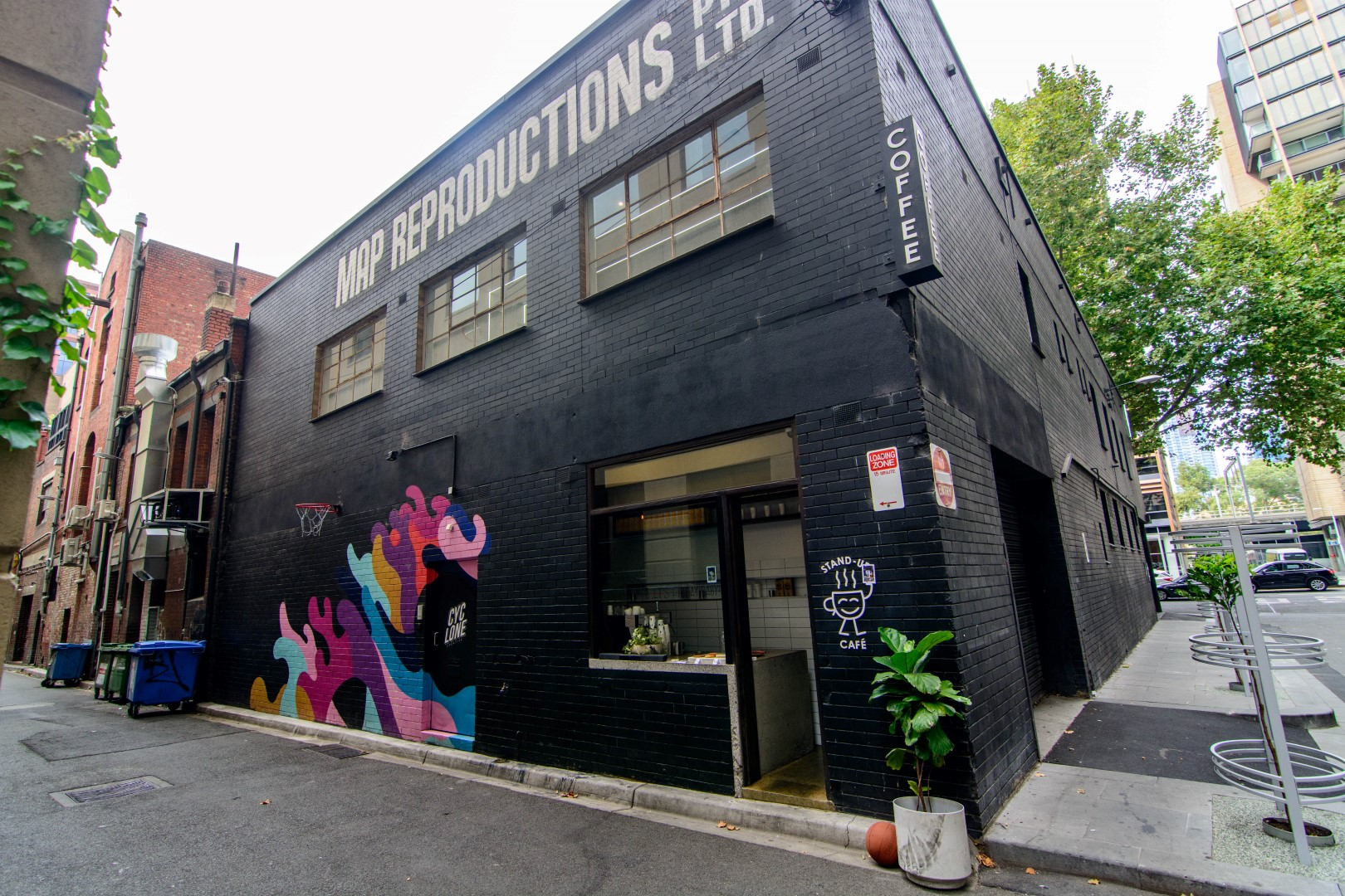 A large black building on a laneway with a colourful mural on the side
