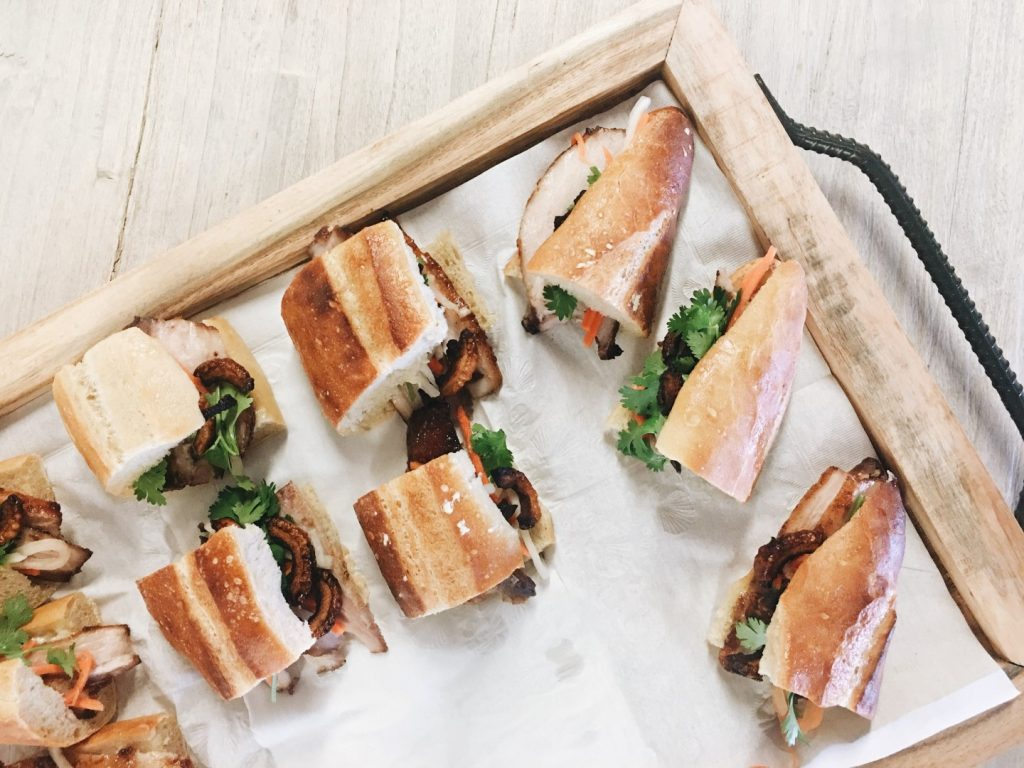A tray of baguette sandwiches on white paper