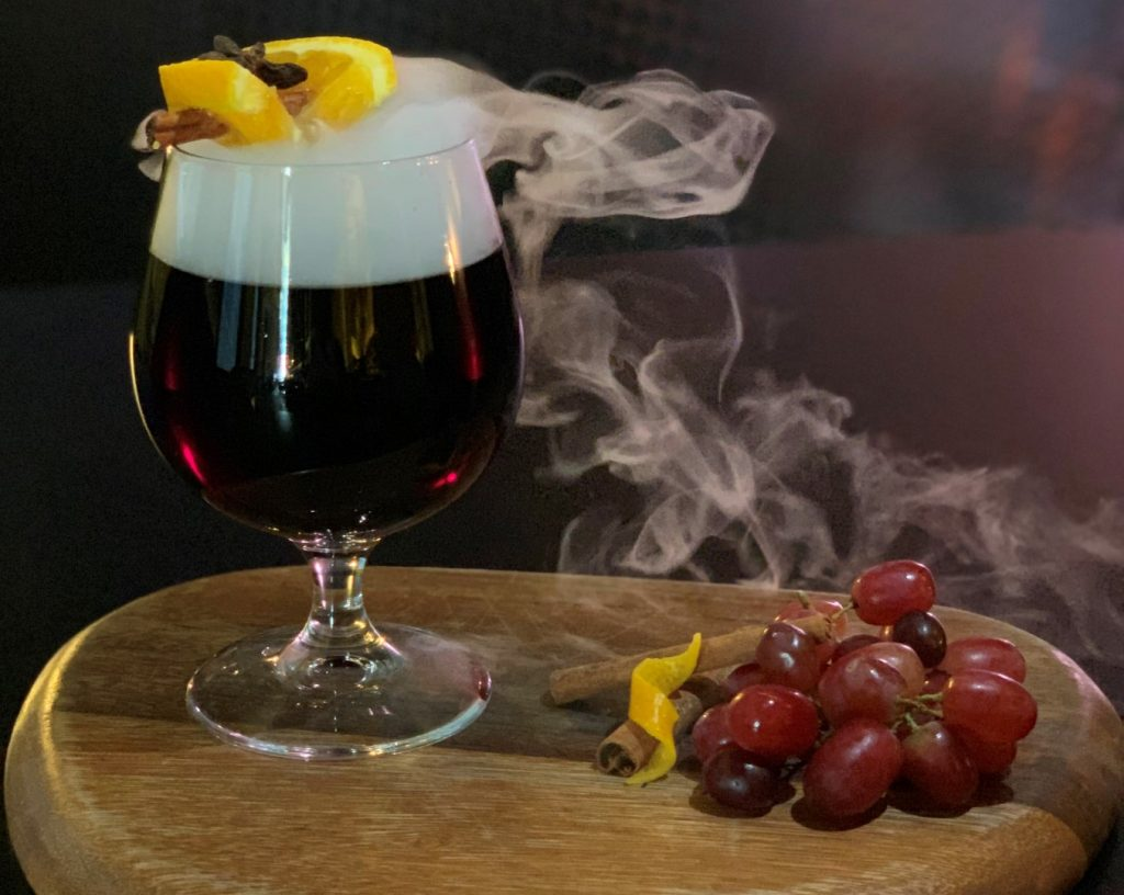 A glass of red wine with a head of white foam and smoke spilling from the top
