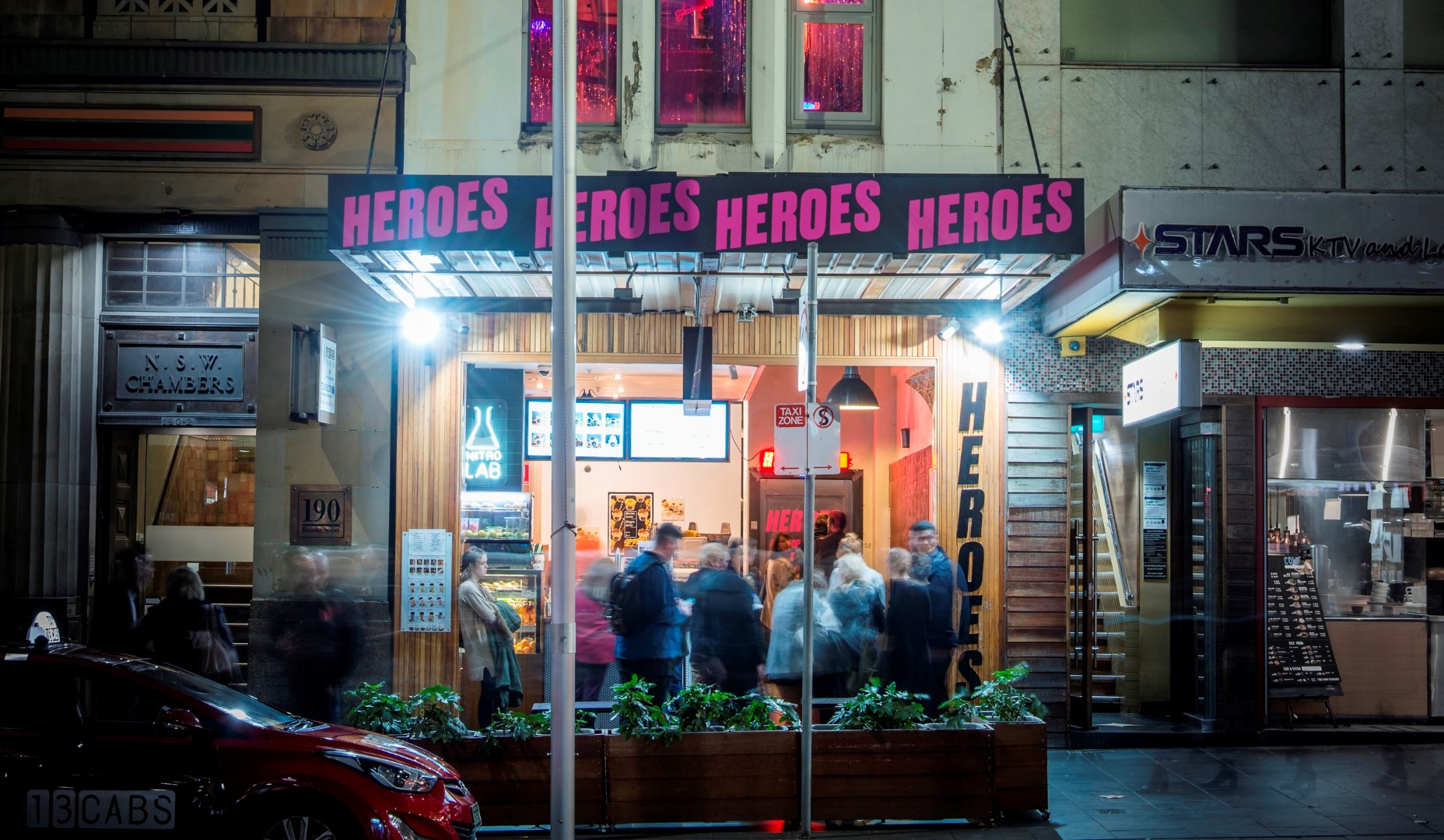 A crowded shopfront on a city street at night