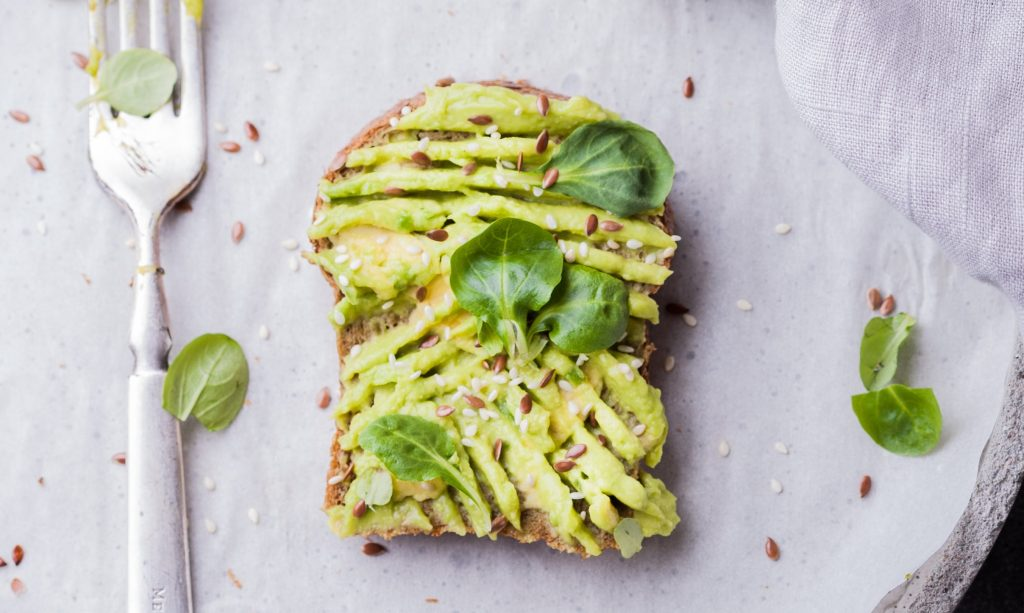 A piece of toast with avocado on a grey plate