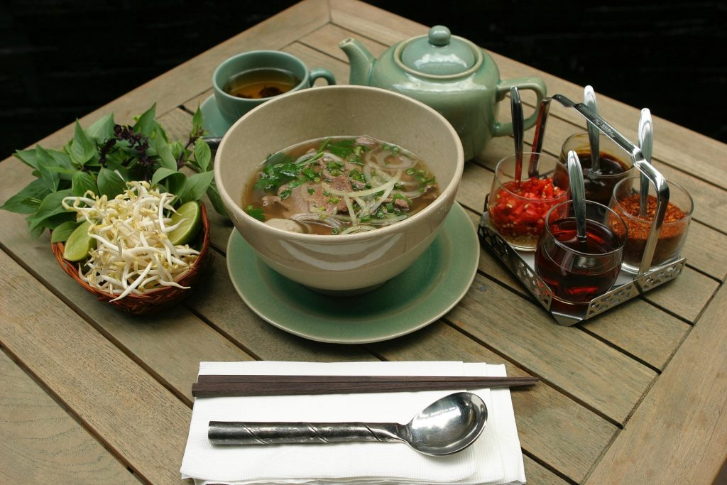 A bowl of pho on a wooden table with cutlery and garnishes