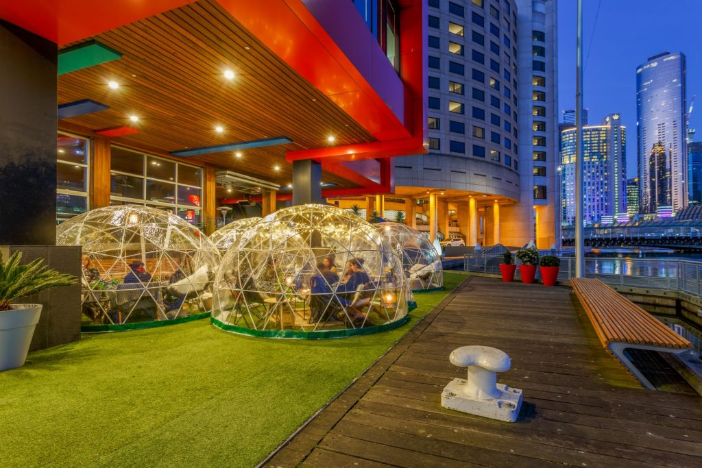 Grassy outdoor area of a pub by the riverside, where large plastic igloos are set up