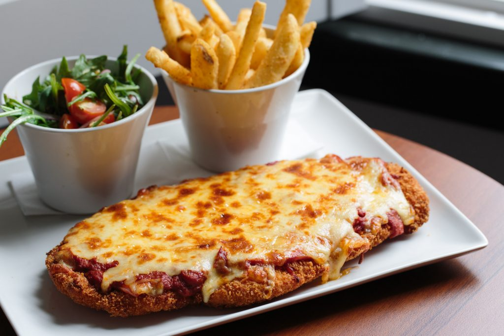 A large chicken parma on a white plate with chips and salad beside it