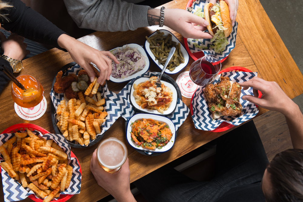 People reaching over a table of food, sharing fried chicken and fries
