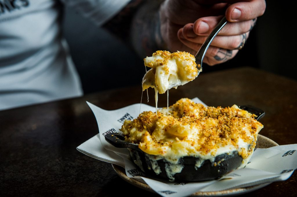 A man's hand scooping a forkful of mac n cheese from a black dish