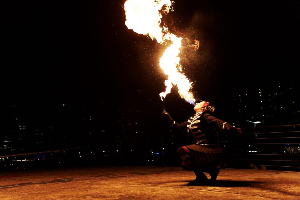 A fire breathing performer blowing fire in the darkness