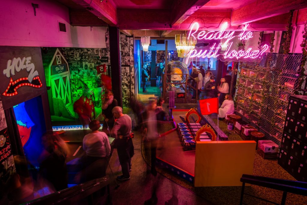 A busy bar with neon signage on the walls