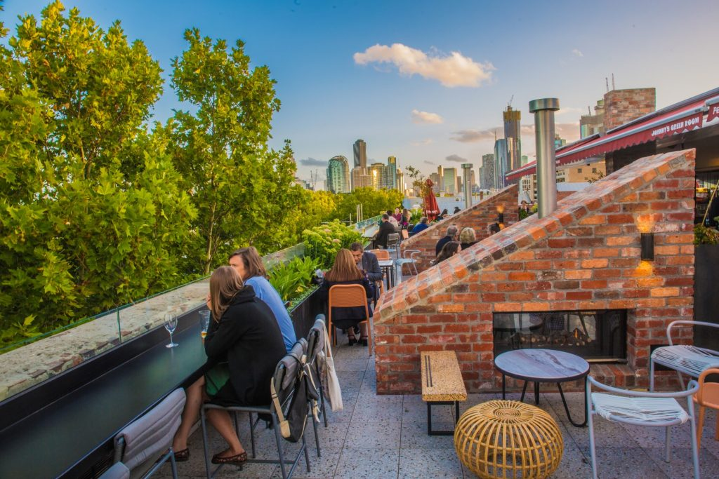 A rooftop bar with people milling at tables