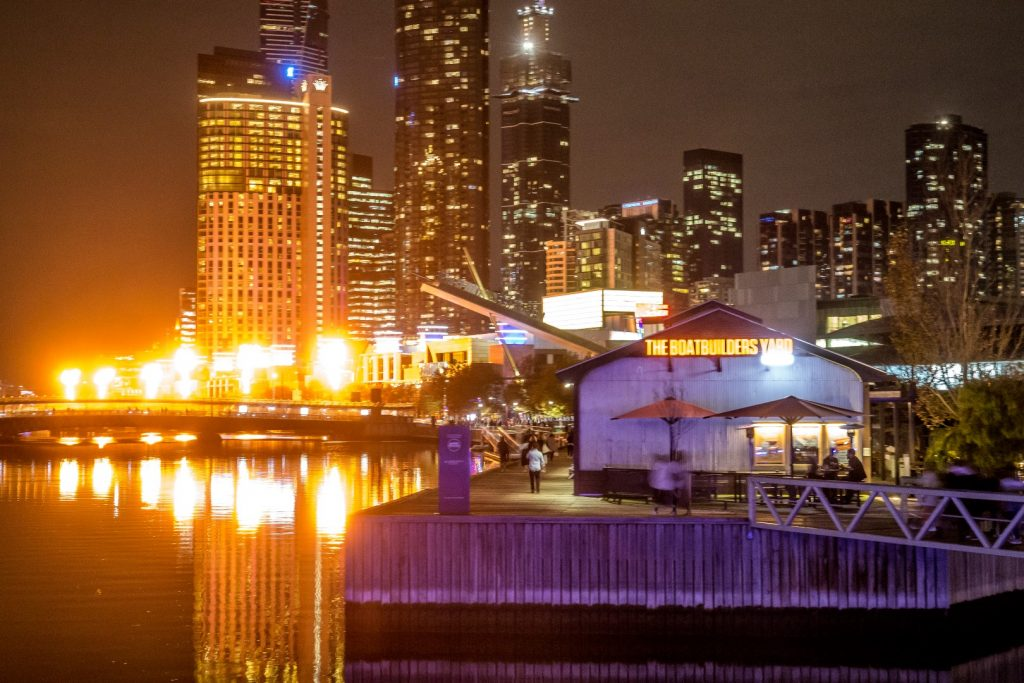 A restaurant on the waterfront with flame towers blazing in the background