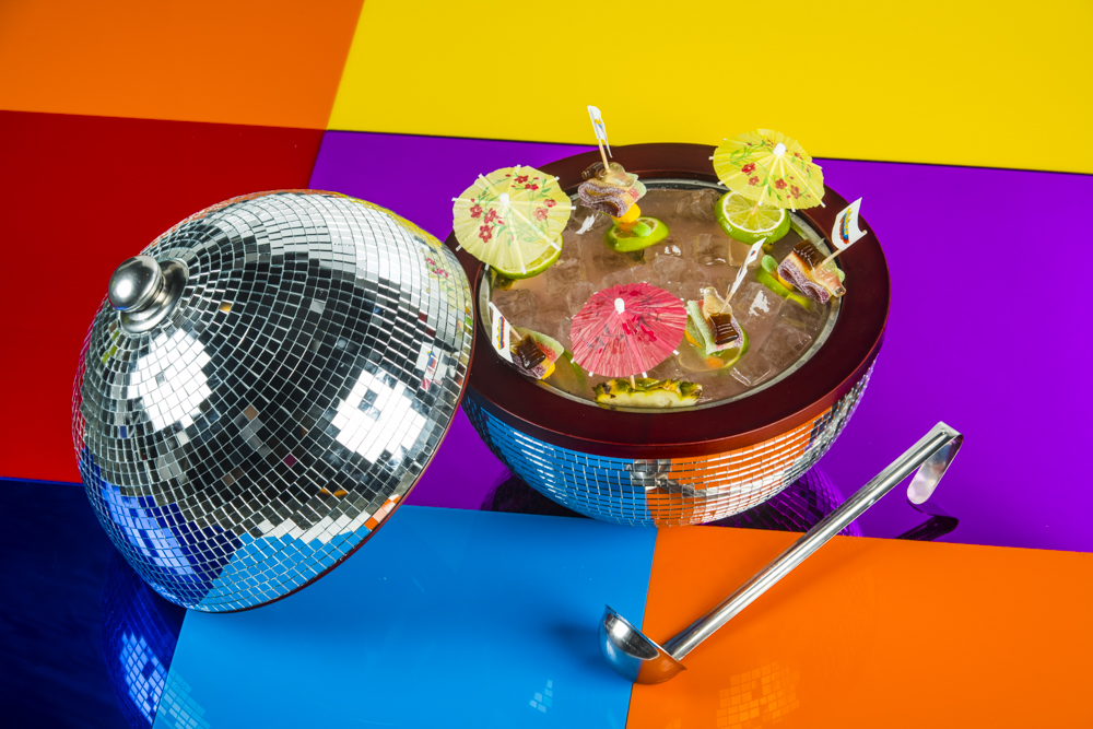 A disco ball cut in half and filled with alcoholic cocktail liquid, mini umbrellas and ice