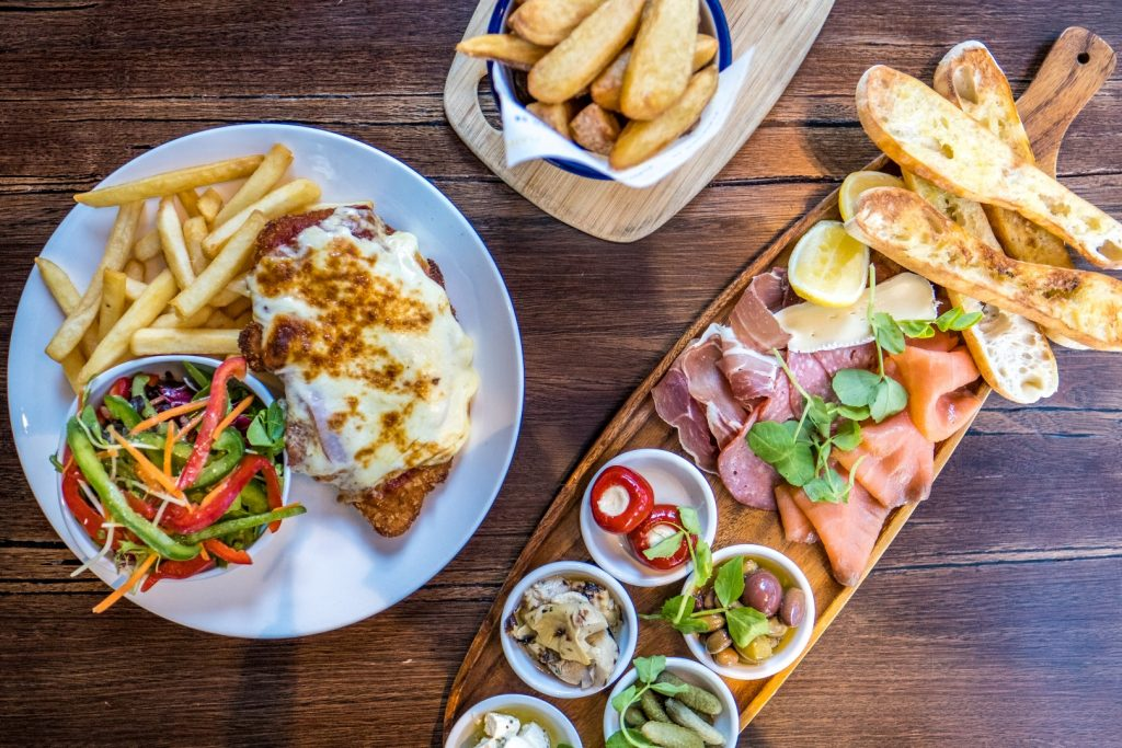 An aerial shot of pub food on a wooden table