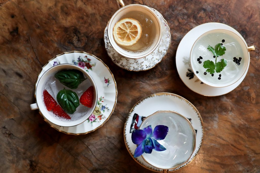 Four tea cups on a table filled with gin and flowers