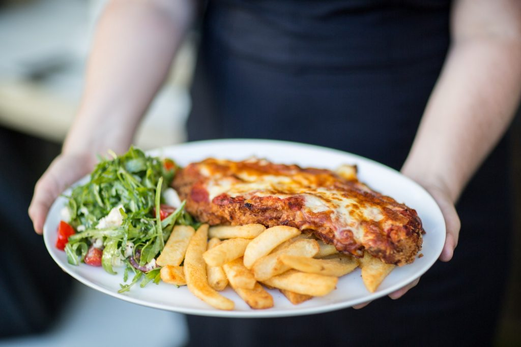 A white plate with chips, a chicken parmagiana and a side salad being held out by a woman's arm