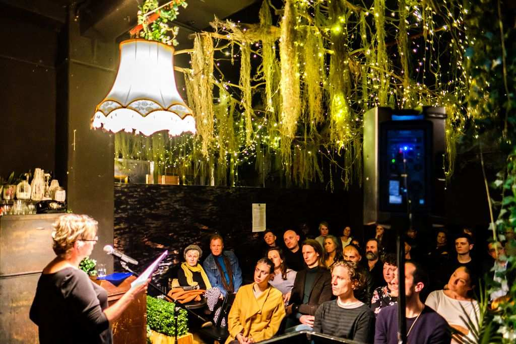 An underground dimly lit bar with plants hanging from the ceiling