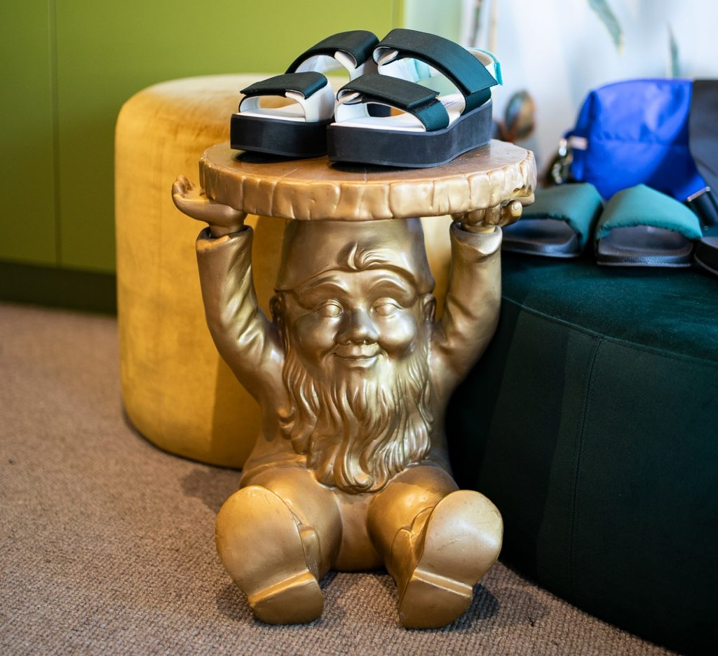A small table shaped like a gnome with a pair of shoes on top