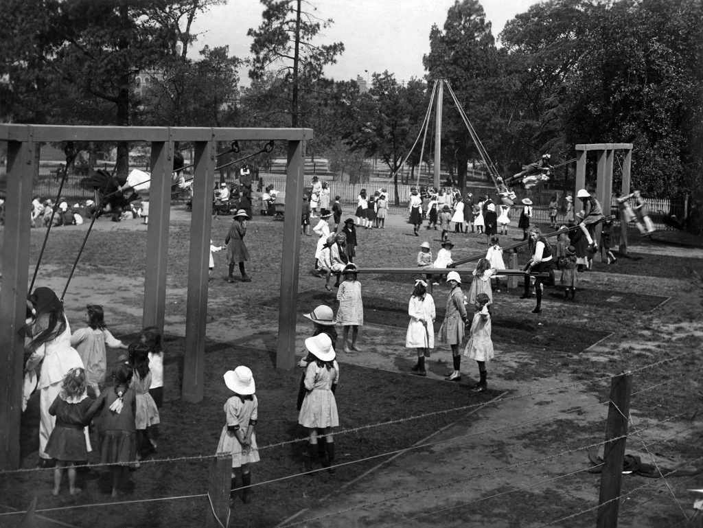 A black and white image of children playing in and old fashioned park