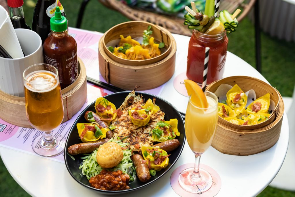 A table laid out with breakfast cocktails and Asian inspired dishes