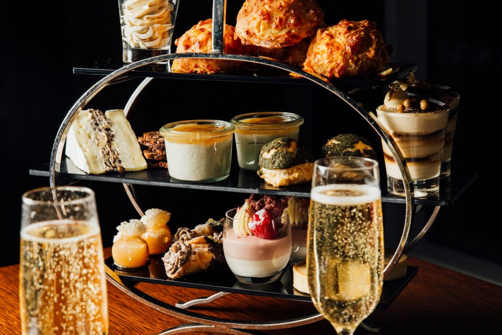 A display with desserts, cheers and sandwiches next to two classes of champagne