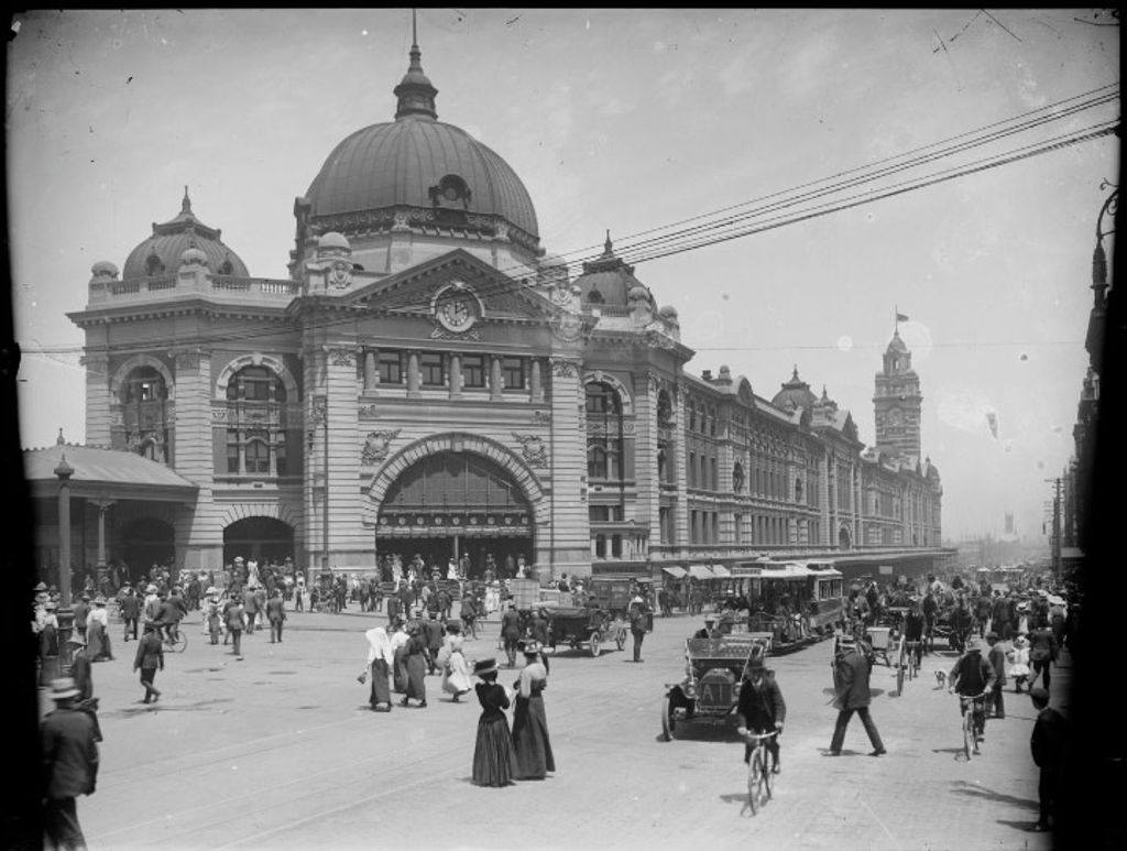 A black and white photo of an old train station with people milling around outside it