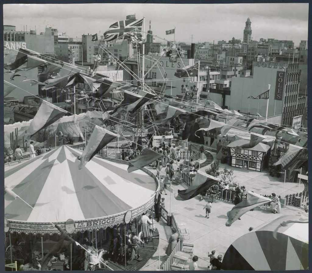 A black and white photo of a carnival on the rooftop of a building