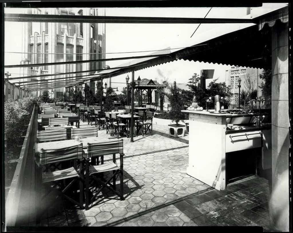 A black and white photo of a cafe on a rooftop