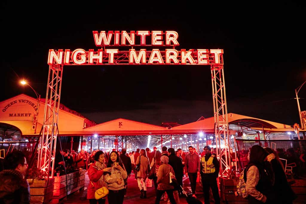 A large glowing red sign spelling out 'winter night market' in front of a bustling night market