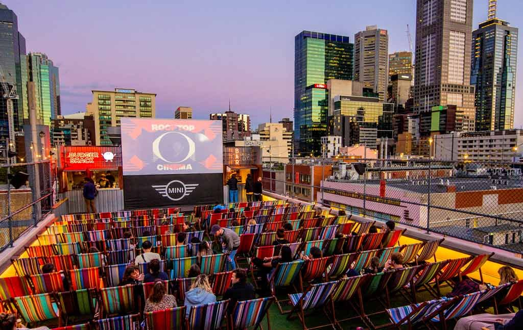 A pop-up cinema set up on the rooftop of a bar with the city skyline in the background