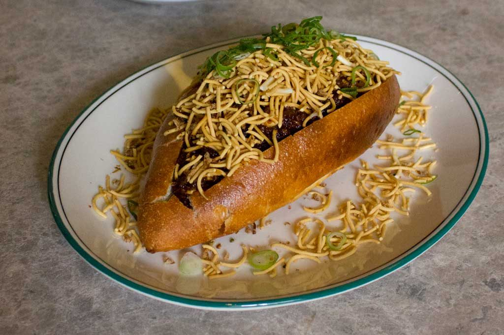 A bread roll on a white plate covered in crispy noodles