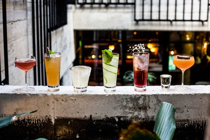 A row of different coloured cocktails in a bar