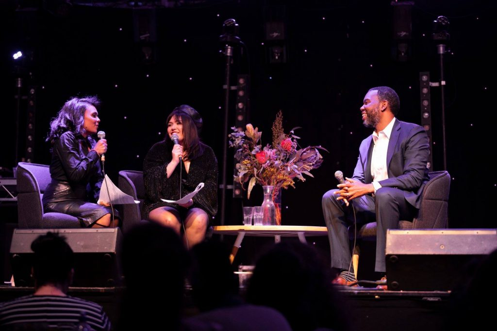 Three people with microphones having a discussion on a stage