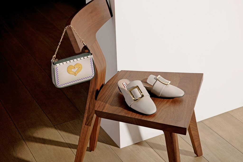 A pair of beige loafers on a wooden chair with a beige handbag hungover the back of the chair
