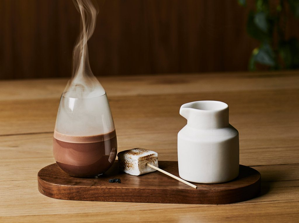 A hot chocolate in a glass with a stream of smoke coming out of it. next to a marshmallow and a white jug
